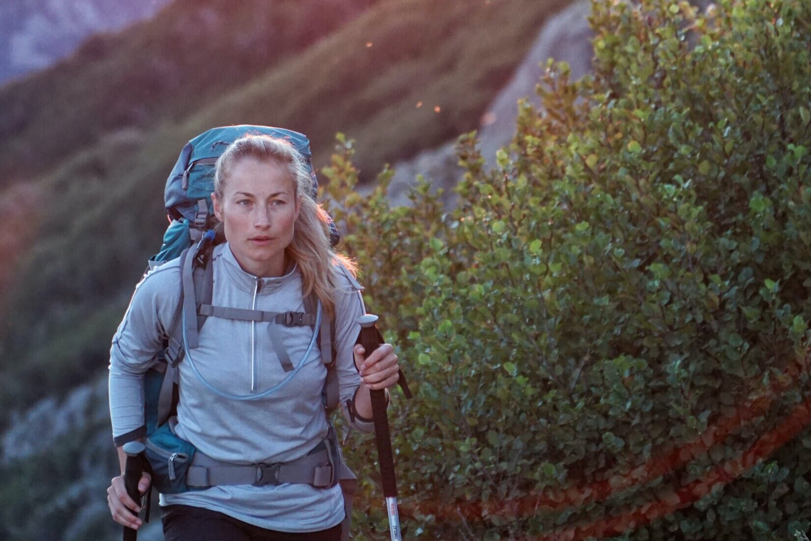 lady walking up hill with hike gear